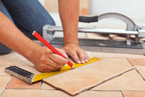 Laying Ceramic Floor Tiles – Man Hands Closeup